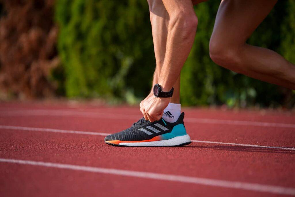 athlète sur piste avec montre cardio gps